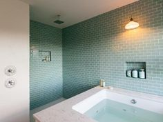 """Glass tile in a mesmerizing shade of """"moonlight,"""" a hue selected by online voters, clads the entire back wall and open shower stall. Custom niches provide space to store soap, beauty and hair care products. Bathroom Spa, Bathroom Toilets, Modern Bathroom, Small Bathroom, Master Bathroom, Bathroom Ideas, Blue Glass Tile, Glass Tiles, Deep Tub"""