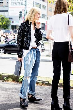 Black bomber jacket, white oversized shirt tucked in to destroyed boyfriend jeans and black pointed toe leather ankle boots with open side vents