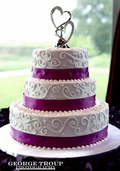 Round 3 tier wedding cake with scrollwork, purple ribbons and hearts cake topper / George Troup Photography