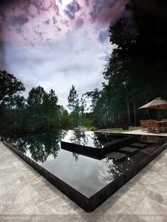 "cool and unique idea of a black reflective infiniti pool with hidden path that provides a ""walk-on-water"" effect when accessing the spa. Award-wining project by Atlantic Landscaping company Selective Designs."