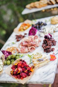 Eine opulente Zusammenstellung aus farbenfrohen Appetithäppchen. Angerichtet auf einer edlen Marmorplatte. Zum Beispiel: Oliven,  Trauben, feiner Schinken, Salami, Käse, Datteln, Pekannüsse. Eine Symphonie der Sinne. Für einen Empfang. Für einen Umtrunk. Als Aperitif.