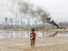 16 July 2015. A boy carries a dog as he stands at a Peruvian police operation to destroy illegal gold mining camps in a zone Mega 14 in the southern Amazon region of Madre de Dios. Peruvian police razed dozens of illegal gold mining camps at the edge of an Amazonian nature reserve this week, part of a renewed bid to halt the spread of wildcatting in a remote rainforest region. The stings at the Tambopata National Reserve were the first in the southeastern region of Madre Dios since December.