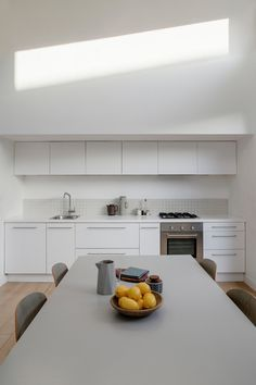 The architectural kitchen in this Harold's Cross cottage has white units and a white Corian countertop that were made to order.