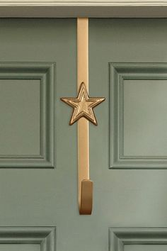 Made from weather resistant metal, this Christmas wreath hanger features a star design and is finished in muted gold. Suitable for indoor or outdoor use, and will fit most wooden or uPVC doors up to 5cm thick. Height 29 x Width 6.5 x Depth 6cm.  100% Iron. Christmas Wreaths, Christmas Decorations, Berry Garland, Wreath Hanger, Front Door Decor, Star Designs, Gold Stars, Indoor, Iron