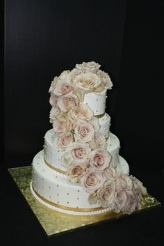 Wedding Cake: White frosting with gold ribbon and dragges. Champagne color cascading fresh roses. www.sugarhillsbakery.com