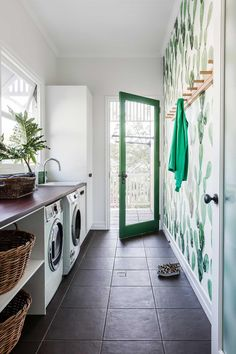 This small laundry has been transformed into functional and stylish space featuring statement wallpaper and smart storage ideas. Photo: Maree Homer