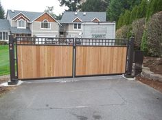 A neat combination of cedar panels with mesh infill on this double swing driveway entrance. #wood #iron #swing #gate #seattle #cedar #security #privacy #automated