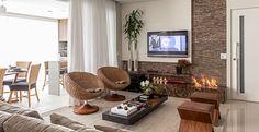 As poltronas giratórias podem ser utilizadas para integrar ambientes, como foi feito neste projeto, que a sala de estar se une à varanda quando se abre a porta e a cortina. Projeto da arquiteta Cristiane Schiavoni.