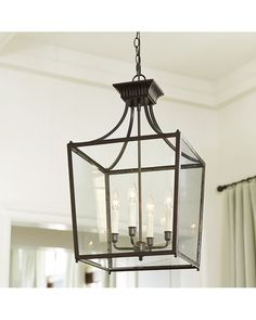Our Sheffield Chandelier's four candle arms are crowned with cream Petite Tapered Drum Chandelier Shades, adding a layer of soft color to the lantern silhouette