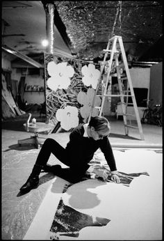 Andy Warhol at work on a large flower painting the Factory, 1965.