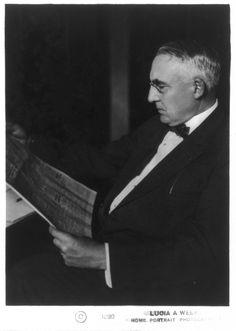 Warren Gamaliel Harding, three-quarters length portrait, seated, looking at newspaper, facing left.