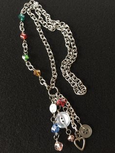 Three vintage white buttons dangle with multi-colored crystal beads on a silver chain with a single heart shaped charm. This asymmetrical look