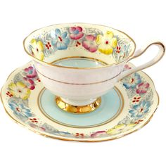 This lovely Royal Albert Bone China Teacup and Saucer is in the blue variation of the Dorothy pattern. In a pale cream that is almost yellow, the