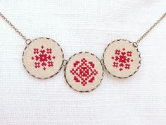 Cross stitch necklace with three royal red ornament in bronze. $28.00, via Etsy.