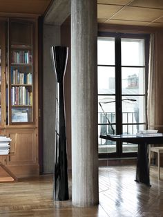 "In the living room, a black Carrara floor lamp by Alfredo Häberli for Luceplan echoes the shape of the column. The Jean Prouvé Trapèze desk is topped with a Kelvin LED lamp designed by Antonio Citterio with Toan Nguyen for Flos. Books rest on a wood Zig Zag chair by Gerrit Rietveld.  Renting the apartment was a dream come true for Claus, who founded his firm in Amsterdam, but had always wanted to live in Paris. ""Why? Anyone who's visited the city will know the answer—it's self-explanatory,""…"