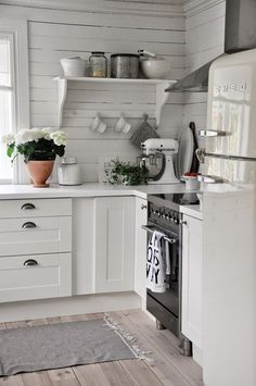Love the clean space-saving cottage kitchen design. The shelf with with bracing bar across for holding cups or stabilization.~~~~Love this kitchen for the white and cabinets and boards~~~ Kitchen Ikea, New Kitchen, Vintage Kitchen, Kitchen Dining, Kitchen Decor, Kitchen Modern, Kitchen Walls, Decorating Kitchen, Kitchen White