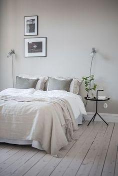 N'encadrer que ses images préférées et une table d'appoint design accueillant un bouquet de fleurs, pour une chambre minimaliste dans laquelle on se sent bien.