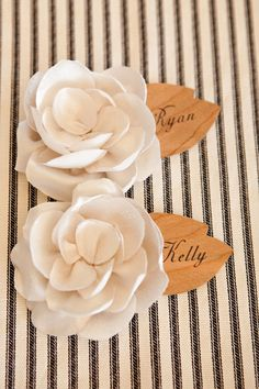 paper flower with name tag, table number and place in empty vases at table