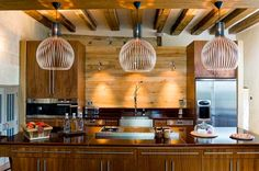 A rustic home in France, with our black Octo 4240 pendants above the kitchen unit. Photo by: Todhunter Earle Interiors.