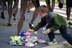 Stacks of Sauconys and Brooks covered in roses obscured the bronze feet of Riverfront Park's Bloomsday sculptures Tuesday evening as  approximately 40 runners from two Spokane running clubs gathered to remember victims of the Boston Marathon bomb att...