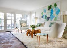 White Rug with Black Fringe, Eclectic, Living Room. Eclectic living room features an emerald green and turquoise abstract art piece over a white sofa with rolled arms adorned with green pillows flanked by chevron skirted tables topped with tall metal lamps facing a burl wood coffee table with blue wingback chair to the left and a cane chair to the right atop a white sheepskin rug with black fringe layered atop a brick hex floor.