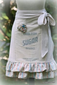 this site doesn't tell you how to make these aprons, but i imagine you have to go to flea markets, yard sales, ect. and find old fabric or sugar bags, or dish rags or something like that and find a way to incorporate them into an apron. if i could only sew...