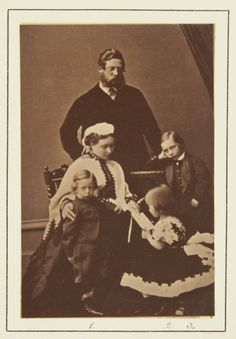 Nov 1865; The Crown Pss seated, her r. hand on P. Henry's shoulder, he stands looking to front; Pss Charlotte seated on stool facing her mother, she looks at book. Crown P. stands behind them, looking downwards; P. William stands to his mother's left