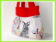 poppige Tasche im Zebra-Look in Natur mit Zebras in Schwarz, Rot, Gelb, Grün und Blau. Die Blende und die Henkel sind aus Canvas in Rot.Das Innenfutte