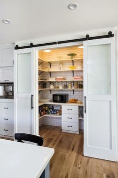 U-shaped pantry with subway tile and sliding farm doors! Now THAT's one amazing kitchen addition!