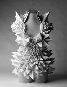"""The costumes that comprise Ecstatic Spaces by Tara Keens-Douglas are made out of paper. Intricately folded and shaped into avant-garde forms, """"The costumes are an ephemeral architecture--fragile and mobile. They are, in a way, architecture of the persona,"""" according to the designer. She believes that the costumes help people to lose their """"inhibitions and becoming something new and different."""""""