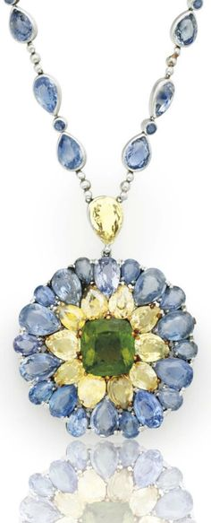 LOUIS COMFORT TIFFANY, TIFFANY & CO. - A SAPPHIRE, COLOURED SAPPHIRE AND TOURMALINE PENDANT NECKLACE, CIRCA 1914. Suspending a circular pendant set with pear-shaped sapphires and yellow sapphires, centring upon a cushion-cut green tourmaline, joined to the bezel-set pear and circular-cut sapphire neckchain by a pear-shaped yellow sapphire link. Signed Tiffany & Co., with exposition mark. #Tiffany #antique