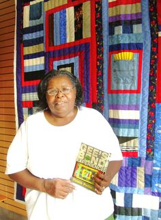 """Tinnie Pettway of Gee's Bend displays her quilts and a book of poems. """"My mama was always writing funny poems, wrote them down on a piece of cardboard. She would read them, making people laugh. I didn't think her poems had a bearing on me, but one day I started writing. People laughed at my words, too."""" Tinnie Pettway still lives in Gee's Bend, a rural community in Alabama's Black Belt."""