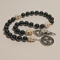 This set of genuine hematite prayer beads was made in honor of my matron goddess THE MORRIGAN. A silver-tone triskele, a symbol closely associated with The Morrigan, adorns one end and a silver-tone raven skull adorns the other end. Carved natural howlite skull spacer beads divide this prayer bead Wiccan, Pagan, Witchcraft, Celtic Goddess, Triple Goddess, Prayer Beads, Divine Feminine, How To Make Beads, Prayers