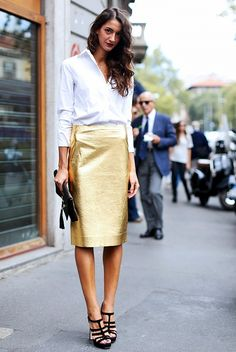 A classic white shirt worn over a H-line gold skirt with a black clutch and black sandals