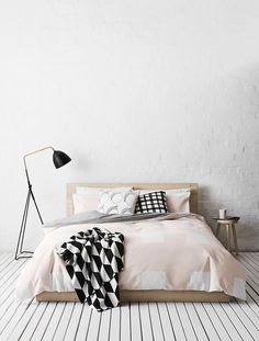 Light pink and black prints = trendy contrast with all-white bedroom