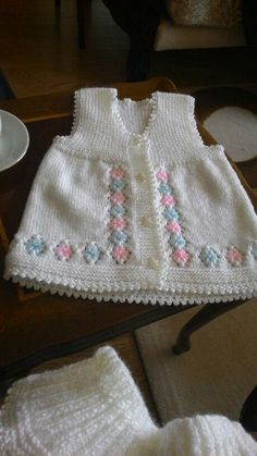 Knitted baby vest. Flowers emb