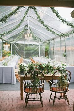 Greenery garland with chandeliers strung between palm trees