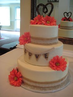 3-tier round wedding cake with burlap and lace trimming and silk flowers.