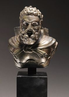 ROMAN BRONZE APPLIQUE BUST OF HERAKLES EMERGING FROM A PALMETTE,  The hero bearded and wrapped in a lionskin; probably from a carriage.  Ca. 2nd Century AD
