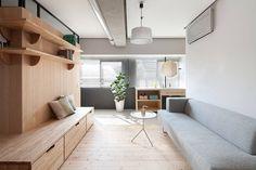 As dimensões compactas deste apartamento em Tóquio, no Japão, não foram um entrave para o escritório Sinato Architects criar um ambiente acolhedor e confortável! A falta de espaço foi contornada com o ótimo aproveitamento da parede, revestida de madeira e transformada em um versátil banco para visitas. Foto: Toshiyuki Yano.