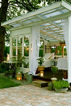 A SUN ROOM IS MADE OUT OF RECYCLED WINDOWS AND DOORS. NOW IT IS A PLACE TO TAKE A SUMMER NAP OR HAVE LUNCH.