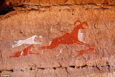 Man's best friend: An early cave painting in Libya of dogs chasing a deer in the Akakus Mo...