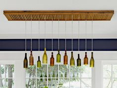 Eleven bottles of beer and wine hang from the ceiling. Before the old house was torn down, Shannon found them strewn in a hedge. A mason cut off the bottoms, then Shannon spray-painted them and strung bulbs with cord to create a bottle chandelier. That's an old bifold door on the ceiling.