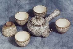 Bun-cheong, brown-porcelain, teapot set with 5 matching cups finished with an intricate floral pattern that was widely used in the early Chosun Dynasty.  From:  http://www.korean-arts.com/tea_ware/teapots/bun-cheong_teapot_set.htm