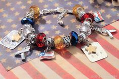 Red, white and blue ring true for a list of patriotic causes. Add yellow beads to support deployed troops or gold stars to recognize fallen soldiers. Then make a mark with flag charms, dog tags or simple silver ribbon charms.