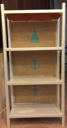 Old bookshelf with a pearl white metallic paint, nautical themed stencils on burlap across the back. To get it to stick, I used double sided fusible webbing and ironed it into place