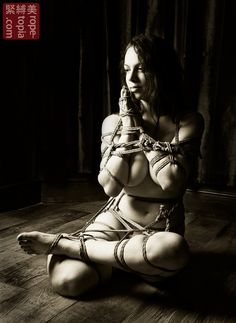 she looks very peaceful.  obviously, this recalls common yoga poses, but when you add rope, they become poetic.