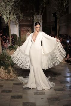 """Vicky Martin Berrocal bridal collection 2015. Fringed long bell sleeves on a mermaid gown with deep V neckline create serious drama in an almost minimalist design. Created for a bride with a modest bust line, on whom this can read as quite chic; whereas on a bride with a more ample bosom, this would come across """"hoochie mama"""". For a winter wedding, add a faux fur scarf/wrap to keep the chill off your neck and chest."""