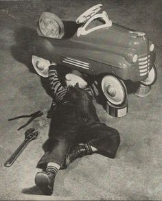 "A child performs ""auto repair"" on his pedal car, 1950."