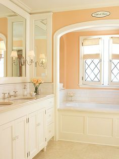 Softly Elegant  An almost-orange shade of coral is a chic update for a white bath. Decorative tile lines the tub and vanity. Lattice window mullions and white trim enhance the traditional look. Small silver sconces mounted on the mirror give this room effortless elegance.